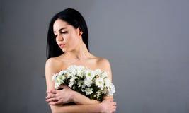 Frau, die ihre Brüste, Abdeckungen mit Blumenstrauß versteckt Bild der Frau hält Bündel reizende Kamillenblumen, grauen Hintergru stockfotografie