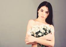 Frau, die ihre Brüste, Abdeckungen mit Blumenstrauß versteckt Dame bedeckt Brüste mit Blumen, grauer Hintergrund Krebs der Brust lizenzfreies stockfoto