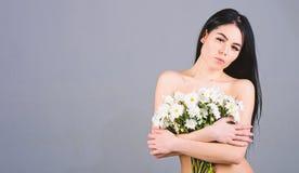 Frau, die ihre Brüste, Abdeckungen mit Blumenstrauß versteckt Krebs des Brustkonzeptes Dame bedeckt Brüste mit den Blumen, grau stockfotos