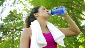 Frau, die ihre Braue und Trinkwasser nach Training im Park abwischt stock footage