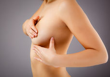 Frau, die ihre Brust überprüft stockbild