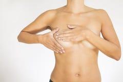 Frau, die ihre Brust auf Krebs prüft Stockfotografie