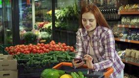 Frau, die ihre Einkaufsliste auf ihrem Smartphone grast stock footage