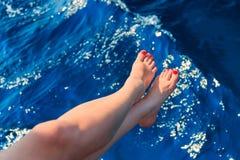 Frau, die ihre Füße über dem Meer hält Lizenzfreie Stockfotografie