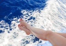 Frau, die ihre Füße über dem Meer hält lizenzfreie stockfotos