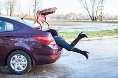 Frau, die ihre Fahrwerkbeine in Autogepäckkabel schwingt Stockfotografie