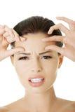 Frau, die ihre Falten auf ihrer Stirn überprüft Lizenzfreie Stockfotos