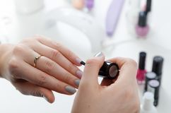 Frau, die ihre Fingernägel malt Lizenzfreie Stockbilder