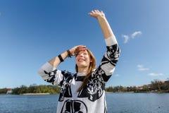 Frau, die ihre Freunde im Park wellenartig bewegt Stockbilder