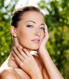 Frau, die ihre frische saubere Haut des Gesichtes streicht stockbilder
