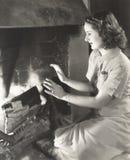 Frau, die ihre Hände durch den Kamin wärmt stockfotografie
