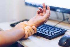 Frau, die ihre Handgelenkschmerz von der Anwendung des Computers hält Stockfotografie