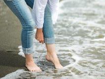 Frau, die ihre Hosen auf dem Strand rollt Lizenzfreies Stockbild