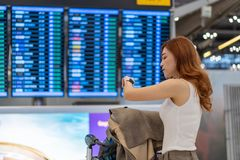 Frau, die ihre intelligente Uhr mit Fluginformationsbrett auf Flughafen betrachtet stockfoto