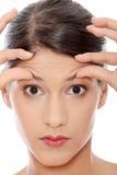 Frau, die ihre Knicken auf ihrer Stirn überprüft lizenzfreies stockbild