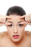 Frau, die ihre Knicken auf ihrer Stirn überprüft stockfoto