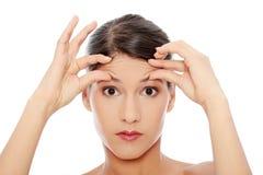 Frau, die ihre Knicken auf ihrer Stirn überprüft lizenzfreie stockbilder