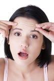 Frau, die ihre Knicken auf ihrer Stirn überprüft Lizenzfreie Stockfotografie