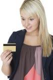 Frau, die ihre Kreditkarte betrachtet Lizenzfreie Stockfotografie