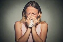 Frau, die ihre laufende Nase durchbrennend niest Stockbild