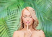 Frau, die ihre Lippen berührt Lizenzfreies Stockbild