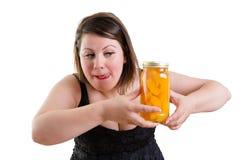 Frau, die ihre Lippen leckt und ein Glas Pfirsiche mustert Stockfotografie
