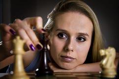Frau, die ihre Maßnahme im Schach trifft Lizenzfreie Stockbilder