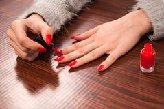 Frau, die ihre Nägel auf Finger in der roten Farbe auf hölzernem Schreibtisch malt lizenzfreies stockbild