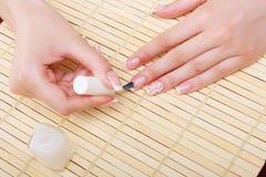 Frau, die ihre Nägel mit Nagellack bedeckt Lizenzfreie Stockfotografie