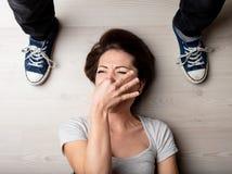 Frau, die ihre Nase gegen den Geruch von Füßen hält lizenzfreies stockbild