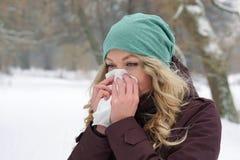 Frau, die ihre Nase im Winter durchbrennt Lizenzfreie Stockbilder