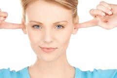 Frau, die ihre Ohren mit den Fingern schließt Stockbild
