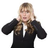 Frau, die ihre Ohren mit einem entsetzten Ausdruck bedeckt Lizenzfreie Stockfotos