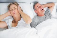 Frau, die ihre Ohren von den Geräuschen des Ehemanns schnarchend blockiert Lizenzfreies Stockfoto