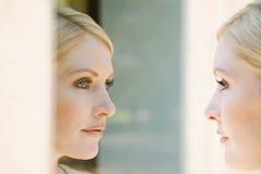 Frau, die ihre Reflexion betrachtet Stockfotos