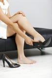 Frau, die ihre Schuhe beseitigt stockfotografie