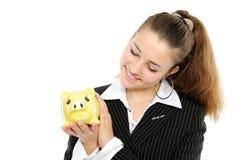 Frau, die ihre Sparungen in einer piggy Querneigung betrachtet Lizenzfreie Stockfotos