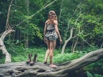 Frau, die ihre Stiefel im Wald entfernt Stockfotos