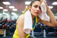 Frau, die ihre Stirn von einem Training trocknet Lizenzfreie Stockbilder