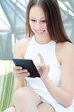 Frau, die ihre Tablette in einem Kaffee verwendet Lizenzfreie Stockfotografie