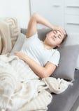 Frau, die ihre Temperatur im Bett nimmt und Kopfschmerzen hat Lizenzfreie Stockfotografie