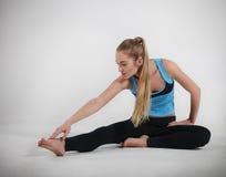 Frau, die ihre Yogaausdehnung tut Lizenzfreies Stockfoto