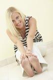 Frau, die ihre Zehen berührt Stockbild