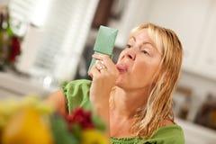 Frau, die ihre Zunge heraus im Spiegel haftet stockfotografie