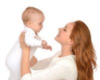 Frau, die in ihrem Armsäuglingskinderbaby-Kindermädchen hält und umarmt Lizenzfreies Stockfoto