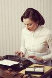 Frau, die in ihrem Büro schreibt Lizenzfreie Stockfotografie