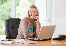Frau, die an ihrem Computer arbeitet, während sie anruft lizenzfreies stockfoto