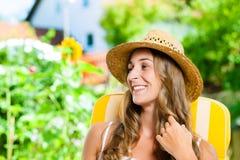 Frau, die in ihrem Garten auf Klubsessel sich bräunt Stockfotos