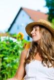 Frau, die in ihrem Garten auf Klubsessel sich bräunt Lizenzfreie Stockfotografie