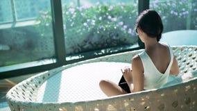 Frau, die an ihrem Luxushaus sitzt stock footage